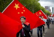 Chinese demonstrators hold flags as they walk outside the Japanese embassy in The Hague. Anti-Japan protests in China over a bitter territorial row died down on Wednesday as authorities apparently sought to ease tensions on the ground, although political leaders maintained their rhetoric