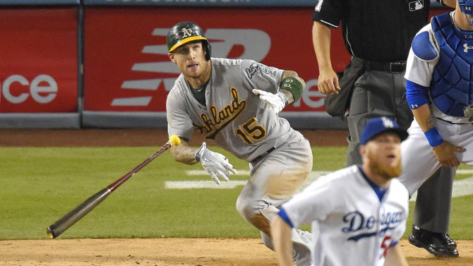 Oakland Athletics' Brett Lawrie, left, runs to first as he hits a two RBI single as Los Angeles Dodgers relief pitcher J.P. Howell watches during the seventh inning of a baseball game, Wednesday, July 29, 2015, in Los Angeles. (AP Photo/Mark J. Terrill)