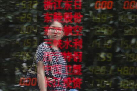 A woman is reflected on an electronic board showing stock information at a brokerage house in Shanghai