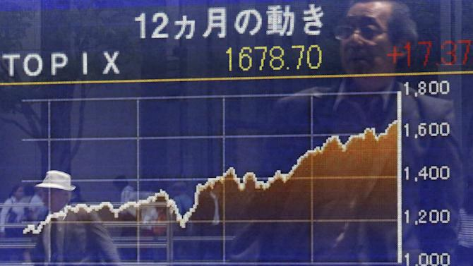 Pedestrians are reflected in an electronic board showing the graph of the recent fluctuations of  the Tokyo Stock Exchange Stock Price Index outside a brokerage in Tokyo