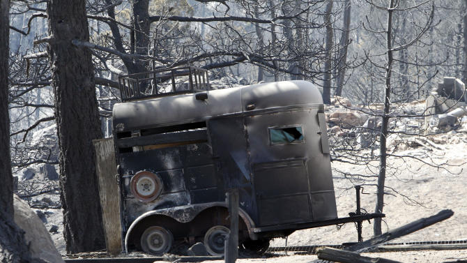 The ruins of a horse trailer destroyed by a wildfire is pictured near Conifer, Colo., on Wednesday, March 28, 2012.  Two people died in the wildfire that started Monday afternoon. (AP Photo/Ed Andrieski)