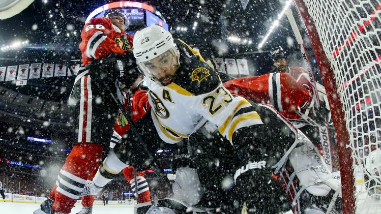 Boston Bruins center Chris Kelly (23) trips over Chicago Blackhawks goalie Corey Crawford (50) who blocked his shot in the first period during Game 5 of the NHL hockey Stanley Cup Finals, Saturday, June 22, 2013, in Chicago. (AP Photo/Bruce Bennett, Pool)