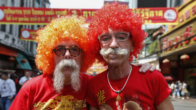 Tourists wear wigs and monkey t-shirts during the celebration of the Chinese New Year in Chinatown in Bangkok