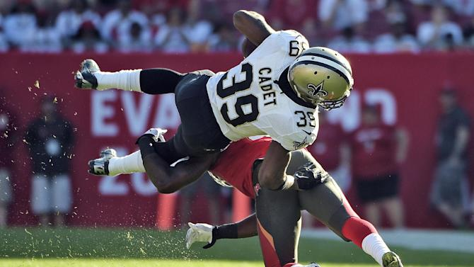 New Orleans Saints running back Travaris Cadet is sent flying on a tackle by Tampa Bay Buccaneers defensive back C.J. Wilson (41) during the fourth quarter of an NFL football game Sunday, Dec. 28, 2014, in Tampa, Fla. (AP Photo/Phelan M. Ebenhack)