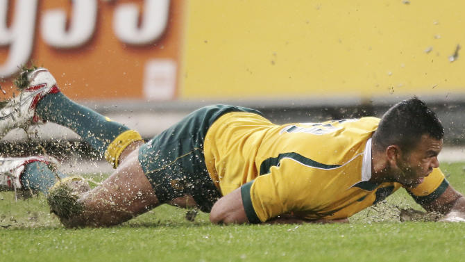 In this Aug. 16, 2014 photo, Australia's Kurtley Beale slides on the pitch after attempting a tackle during their Bledisloe Cup rugby union test match against New Zealand in Sydney. After a week of turmoil involving a star player and speculation over his own coaching future, Ewan McKenzie has recalled Christian Leali'ifano to fill in for the suspended Kurtley Beale in Australia's midfield for their Bledisloe Cup test against New Zealand Saturday, Oct. 18, 2014. (AP Photo/Rick Rycroft)