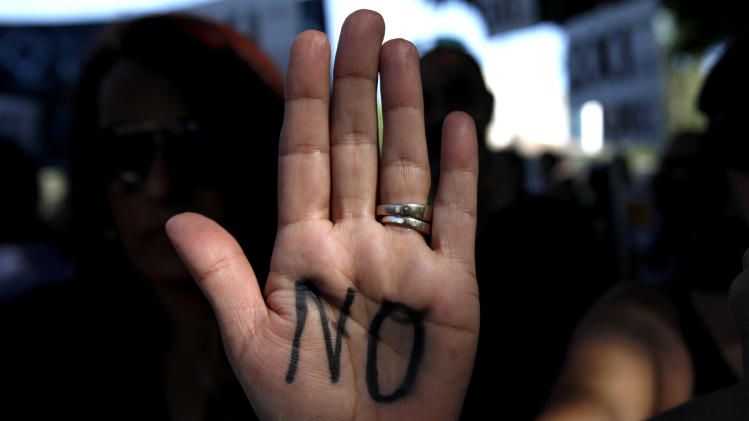 "A protestor who wrotes ""NO"" on her hand during an anti-bailout protest outside of the Cyprus' parliament in capital Nicosia, Tuesday, April 30, 2013. Cyprus' lawmakers are voting Tuesday on a multi-billion bailout agreement aimed at preventing the country from going bankrupt. The 56-seat parliament is expected to narrowly approve the 23 billion-euro ($30 billion) deal that the country struck with its euro partners and the International Monetary Fund last month. (AP Photo/Petros Karadjias)"