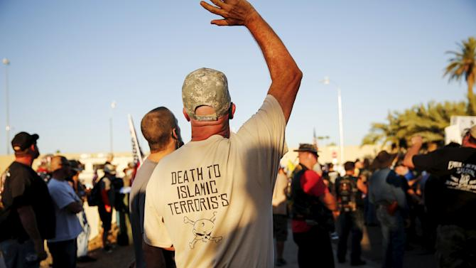 "Demonstrator waves during ""Freedom of Speech Rally Round II"" across from the Islamic Community Center in Phoenix"