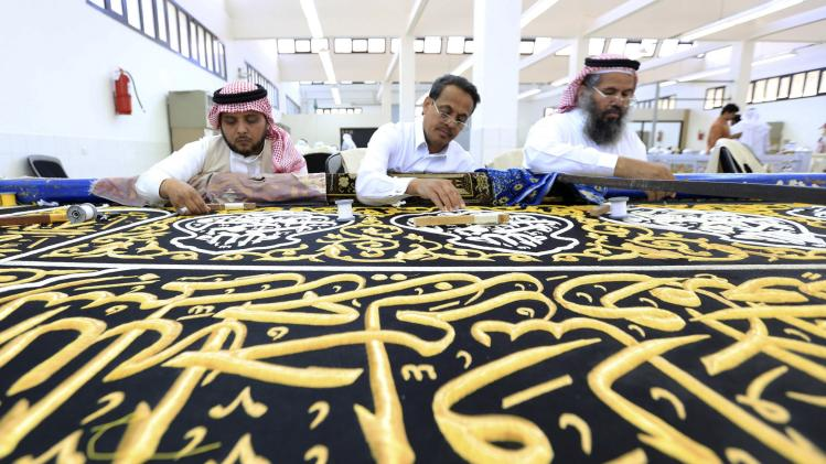 Workers embroider the Kiswa, a silk cloth covering the Holy Kaaba, at a factory in the holy city of Mecca