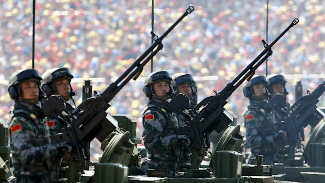 Soldiers of China's People's Liberation Army hold guns while standing in armored vehicles during the military parade to mark the 70th anniversary of the end of World War Two, in Beijing