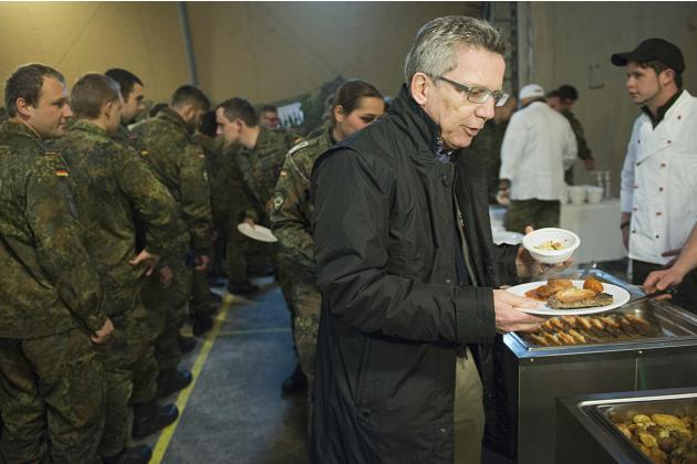 German Defence Minister de Maiziere gets some food during Christmas celebrations with KFOR soldiers in Novo Selo