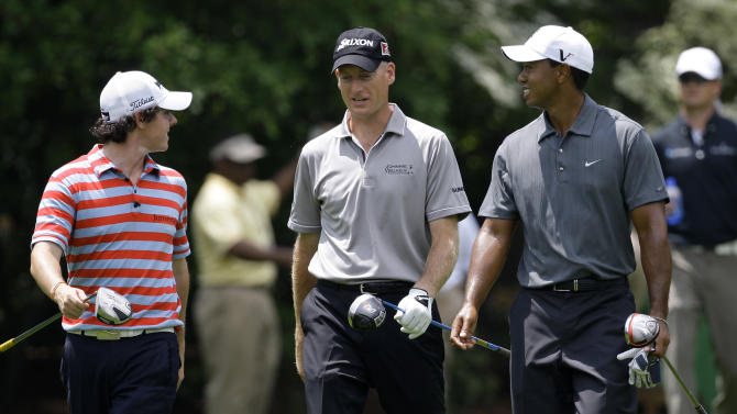 "FILE - In t his June 2, 2010, file photo, Rory McIlroy, left, from Northern Ireland, , Jim Furyk, center, and Tiger Woods walk down the 13th fairway during the skins game at the Memorial golf tournament at Muirfield Village Golf Club in Dublin, Ohio. McIlroy is No. 1 in the world, an Furyk says that makes him a marked man at the Ryder Cup. He said the 23-year-old from Northern Ireland is a ""present day Tiger Woods,"" and that everyone wants to see McIlroy and Woods in Sunday singles. The Ryder Cup is next week at Medinah, outside of Chicago. (AP Photo/Tony Dejak, File)"