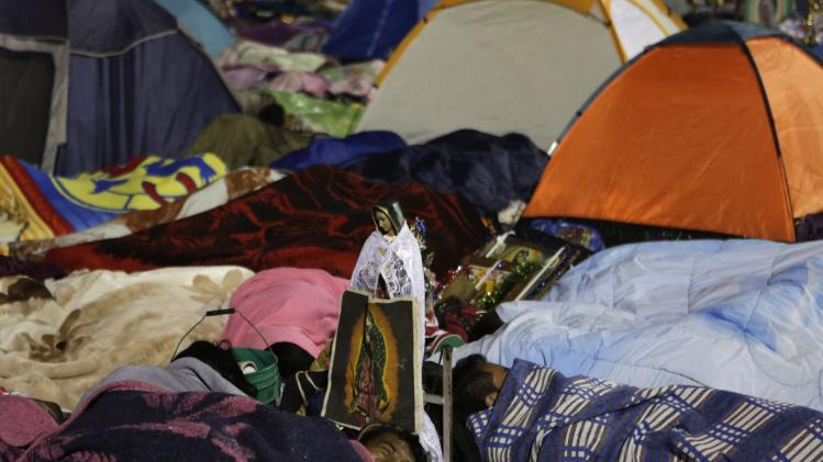 Pilgrims sleep next to an image and a statue of the Virgin of Guadalupe inside the Basilica of Guadalupe during the annual pilgrimage in Mexico City