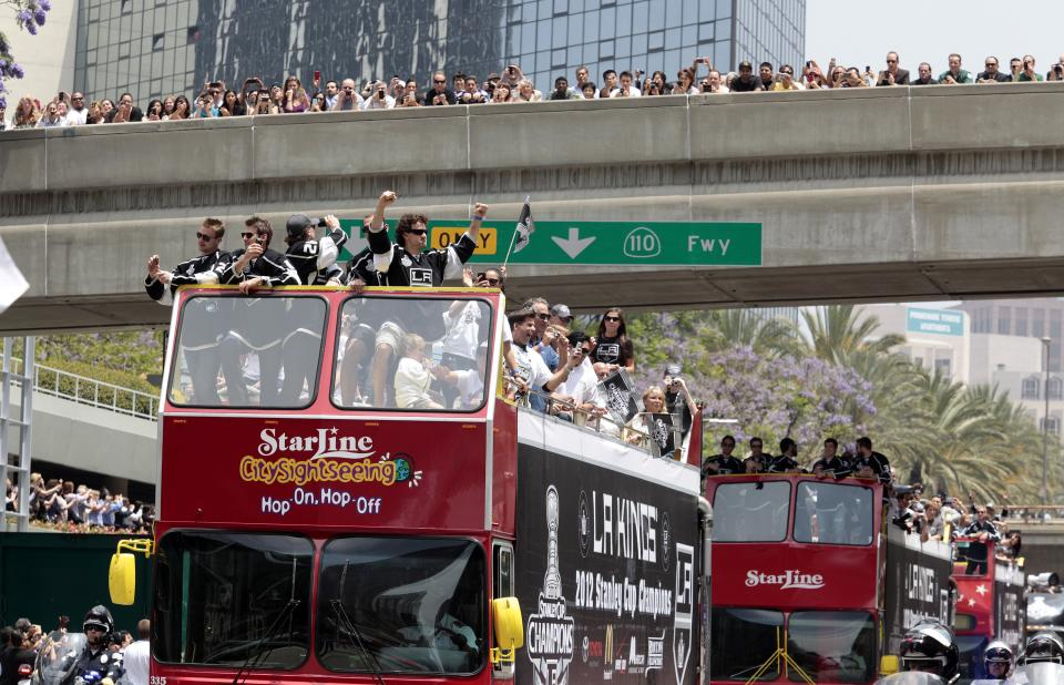 Hockey fans watch from a bridge as the Los Angeles Kings ride atop buses during a parade celebrating the team's NHL hockey Stanley Cup championship in Los Angeles, Thursday, June 14, 2012. (AP Photo/Richard Vogel)
