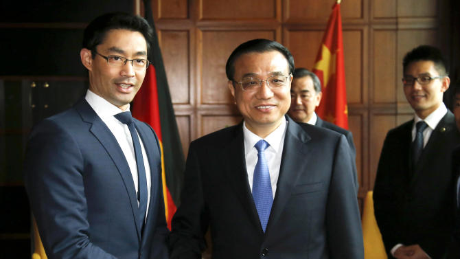 German Economy Minister Philipp Roesler, left, shakes hands with Chinese Premier Li Keqiang prior to a meeting in Berlin Monday May 27, 2013. (AP Photo/Tobias Schwarz,Pool)