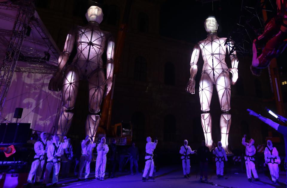 Actors perform with giant puppets during an open air event in front of the Munich opera, southern Germany, on Friday, June 28, 2013. Munich celebrates the200. birthday of composers Richard Wagner and Guiseppe Verdi. (AP Photo/Matthias Schrader)
