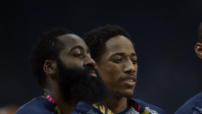 James Harden (L) and Derrick Rose of the U.S. pose with the trophy after winning their Basketball World Cup final game against Serbia in Madrid