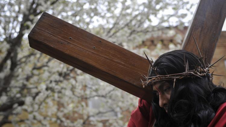 Jose Miguel Almaraz, dressed as Jesus Christ, takes part in 'Way of the Cross' procession through the streets of Philadelphia during Good Friday