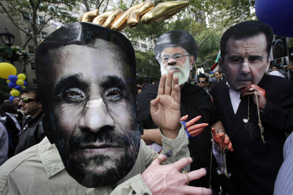 Men wearing masks of Iranian President Mahmoud Ahmadinejad, left, Iranian Ayatollah Ali Khamenei, center, and Syrian President Bashar al-Assad, right, participate in a protest led by Iranian Americans and Syrian Americans outside the United Nations, Wednesday, Sept. 26, 2012 in New York. (AP Photo/Mark Lennihan)