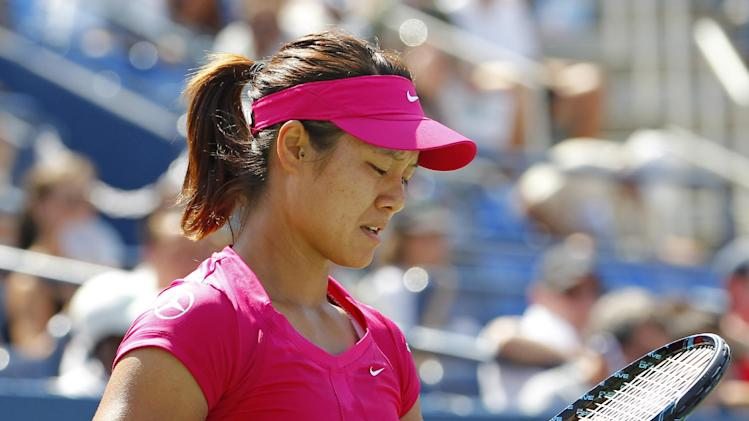 China's Li Na adjusts the strings on her racket  during her match against Britain's Laura Robson in the third round of play at the 2012 US Open tennis tournament,  Friday, Aug. 31, 2012, in New York. Li Na lost the match. (AP Photo/Paul Bereswill)