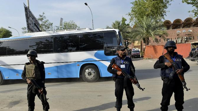 Security personnel stand guard as buses carrying the Zimbabwe and Pakistan cricket teams arrive at the Gaddafi Cricket Stadium in Lahore, northeast Pakistan on May 27, 2015