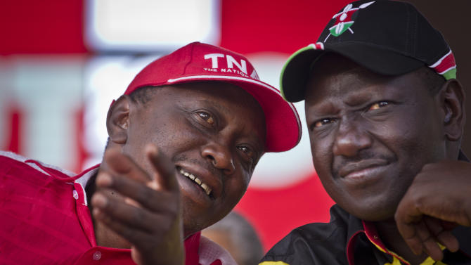 Kenyan Presidential candidate Uhuru Kenyatta, left, and his running mate William Ruto, right, talk together at the final election rally of Kenyatta's The National Alliance party at Uhuru Park in Nairobi, Kenya Saturday, March 2, 2013. Kenya's top two presidential candidates - Uhuru Kenyatta and Raila Odinga - held their final rallies Saturday before large and raucous crowds ahead of Monday's vote, which is the first nationwide election since Kenya's December 2007 vote descended into tribe-on-tribe violence that killed more than 1,000 people. (AP Photo/Ben Curtis)