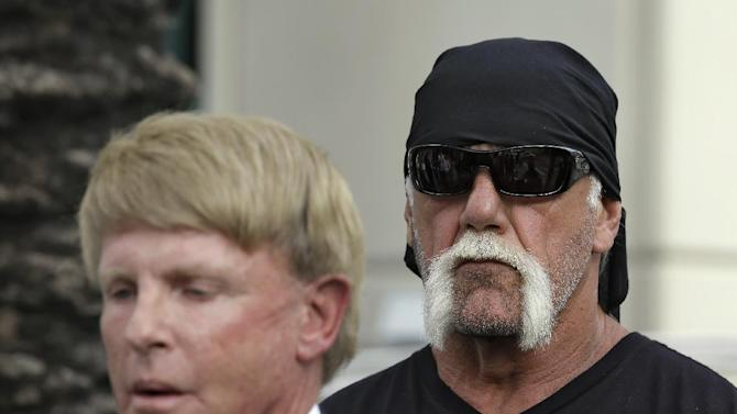 """Reality TV star and former pro wrestler Hulk Hogan, whose real name is Terry Bollea, looks on as his attorney David Houston speaks during a news conference Monday, Oct. 15, 2012 at the United States Courthouse in Tampa, Fla. Hogan says he was secretly taped six years ago having sex with the ex-wife of DJ Bubba """"The Love Sponge"""" Clem. Portions of the video of Hogan and Heather Clem were posted on the online gossip site Gawker. (AP Photo/Chris O'Meara)"""