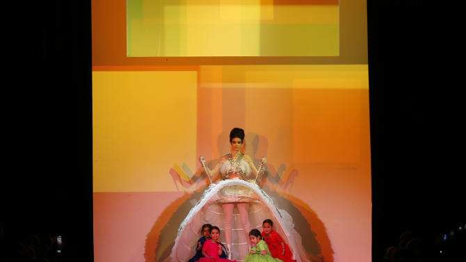Children  appear under the weeding gown worn by model for French fashion fashion designer Jean-Paul Gaultier's Spring-Summer 2013 Haute Couture fashion collection, presented in Paris, Wednesday, Jan.23, 2013. (AP Photo/Jacques Brinon)