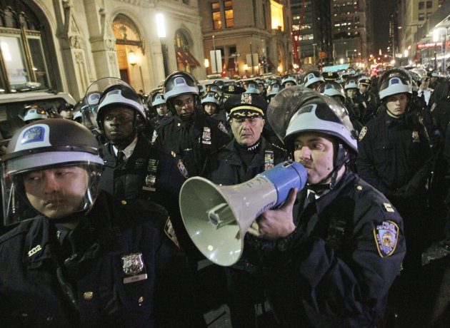 FILE- In this Nov. 15, 2011 file photo, police officers disperse Occupy Wall Street protesters near the encampment at Zuccotti Park in New York. A survey by the Associated Press shows that since the protests began, the Occupy Wall Street protests have cost local taxpayers at least $13 million in the 18 cities with active protests. (AP Photo/Mary Altaffer, File)