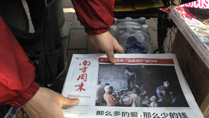 A vendor adjusts a stack of latest edition of Southern Weekly newspaper at a newsstand near the headquarters of the newspaper in Guangzhou, Guangdong province, China Thursday, Jan. 10, 2013. The influential weekly newspaper whose staff rebelled to protest heavy-handed censorship by China's government officials published as normal Thursday after a compromise that called for relaxing some intrusive controls but left lingering ill-will among some reporters and editors. (AP Photo/ Vincent Yu)