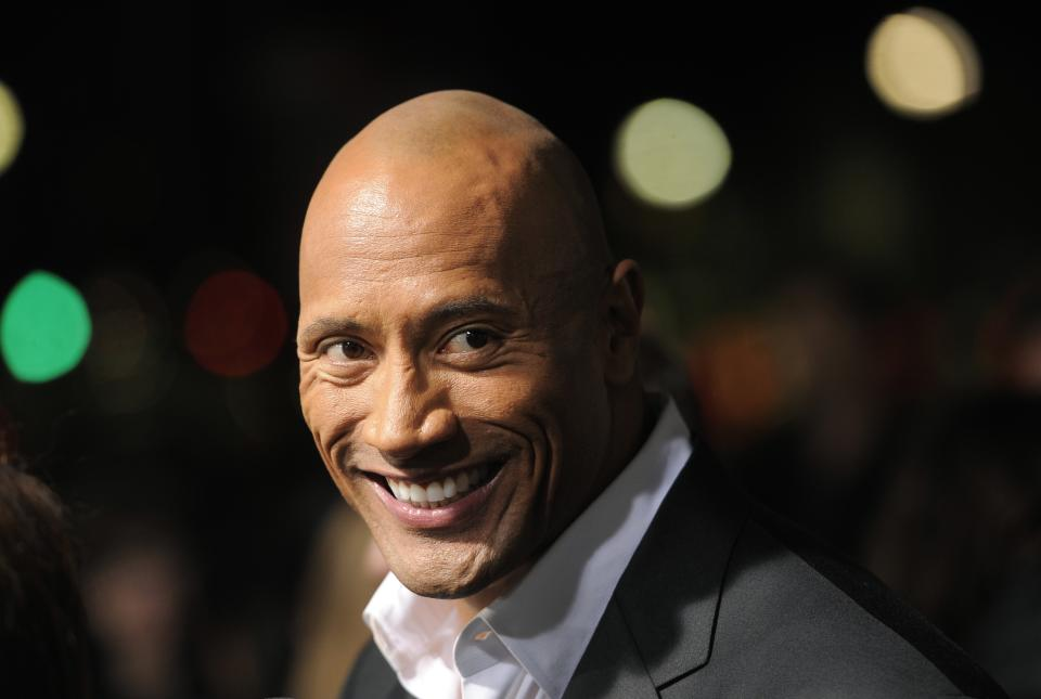 "Dwayne Johnson, a cast member in ""G.I. Joe: Retaliation,"" looks down the carpet at the Los Angeles premiere of the film at the TCL Chinese Theatre on Thursday, March 28, 2013 in Los Angeles. (Photo by Chris Pizzello/Invision/AP)"