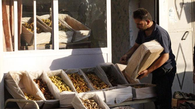 A man arranges sweets into boxes in a market ahead of the upcoming Muslim Eid al-Adha holiday in Manbej