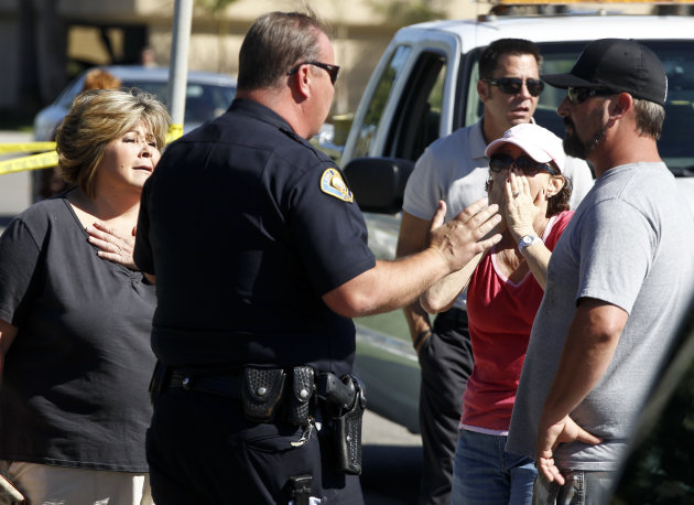 A police officer talks to onlookers near the site where six people were killed and three were wounded in a shooting at a hair salon in Seal Beach, Calif., Wednesday, Oct. 12, 2011. The six deaths were