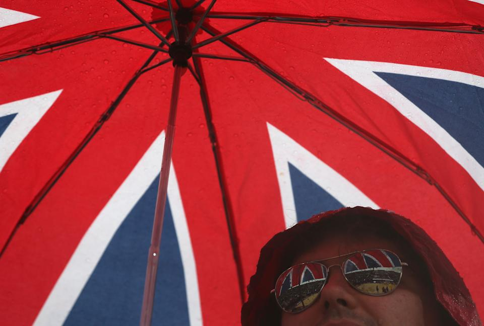 A fan holds an umbrella during a rainy afternoon at the Beach Volleyball venue at the 2012 Summer Olympics, Sunday, July 29, 2012, in London. (AP Photo/Petr David Josek)