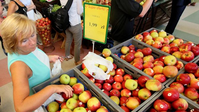 A woman is picking apples to buy at 1.99 zlotys (euro 0.47) per kilogram at a supermarket in Warsaw, Poland, Wednesday, Aug. 6, 2014, the day when fruit farmers marched in the city intending to encourage Poles to eat more apples and this way offset the expected negative effects of a ban that Russia imposed last week on Polish fruit, a move seen as retaliation for European Union sanctions on Moscow over Ukraine. Poland is among Russia's largest suppliers of apples. (AP Photo/Czarek Sokolowski)