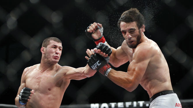 Rashid Magomedov, left, from Russia, left, fights Elias Silverio, from Brazil, during their UFC lightweight mixed martial arts bout in Barueri, on the outskirts of Sao Paulo, Brazil, early Sunday, Dec. 21, 2014. (AP Photo/Andre Penner)