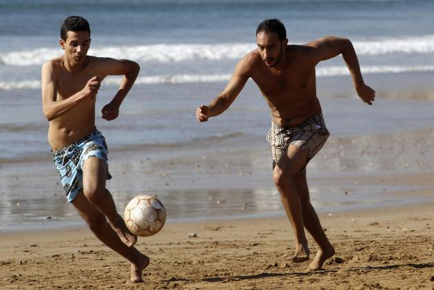 Moroccan youths play soccer at the Atlantic beach in Agadir