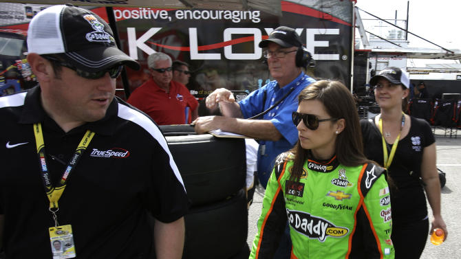 Danica Patrick, center, walks to her hauler in the garage area during a practice session for the NASCAR Daytona 500 Sprint Cup Series auto race at Daytona International Speedway, Friday, Feb. 22, 2013, in Daytona Beach, Fla. (AP Photo/John Raoux)