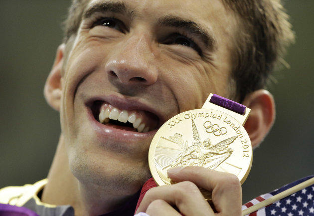 United States' Michael Phelps poses with his gold medal for the men's 4x200-meter freestyle relay swimming final at the Aquatics Centre in the Olympic Park during the 2012 Summer Olympics in London, Tuesday, July 31, 2012. (AP Photo/Matt Slocum)
