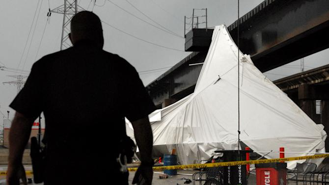 An officer from the Terminal Railroad Police Department surveys a party tent from Kilroy's Sports Bar in St. Louis as it rests against a railroad trestle near the bar after storm winds blew through the area following a baseball game between the St. Louis Cardinals and Milwaukee Brewers at nearby Busch Stadium Saturday, April 28, 2012. One person died Saturday and more than a dozen were taken to a hospital with injuries after high winds blew over a beer tent near Busch Stadium in St. Louis. (AP Photo/Sid Hastings)