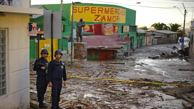 Navy officers patrol a main street covered with debris at Chanaral town