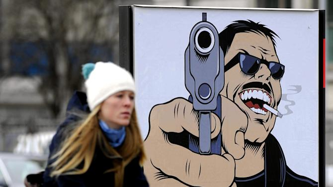 FILE - In this Jan. 11, 2011 file photo, a woman passes a poster reading: 'Weapons Monopoly for Criminals? No' in Zurich, Switzerland. In September 2001, a man named Friedrich Leibacher went on a rampage in the regional parliament in the wealthy northern Swiss city of Zug, killing 14 people and himself, apparently over a grudge against a local official. The massacre, along with a campaign to reduce Switzerland's high level of gun suicide, led to a referendum last year. It proposed that military-issued firearms must be locked in secure army depots and would have banned the sale of fully automatic weapons and pump-action rifles. (AP Photo/Keystone/Walter Bieri, File)