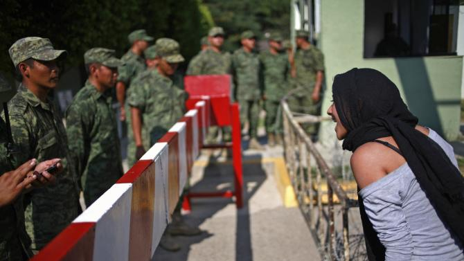 Relatives of missing students demonstrate outside the military zone of the 27th infantry battalion in Iguala