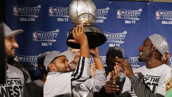 San Antonio players Manu Ginobili, left, and DeJuan Blair, right, watch as Patty Mills raises the Western Conference trophy after the Spurs defeated the Memphis Grizzlies 93-86 in game 4 of the NBA basketball playoff series, Monday, May 27, 2013, in Memphis, Tenn. The Spurs advance to the NBA finals. (AP Photo/Pool-Rogelio V. Solis)