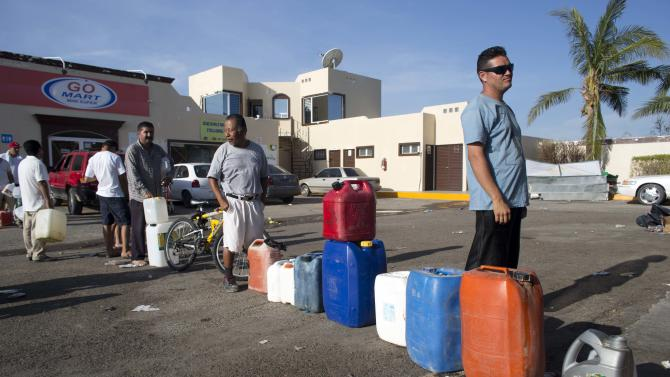 People wait in line to fill up their jugs and bottles with fuel at a gasoline station in San Jose de los Cabos, Mexico, Thursday, Sept. 18, 2014. After Hurricane Odile roared past, residents of the resort state of Baja California Sur struggled with a lack of power and running water and formed long lines for emergency supplies. The remnants of Odile is now taking aim at the U.S. Southwest. (AP Photo/Dario Lopez-Mills)