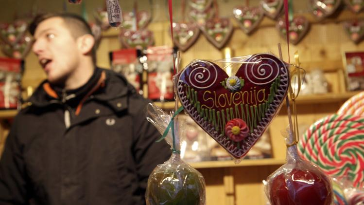 A man sells a gingerbread heart at a market in Ljubljana