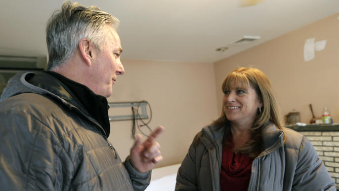 Donald Denihan, left, talks with Kerry Ann Troy during a visit to the Troy family house, under renovation after it was seriously damaged during Superstorm Sandy, in Long Beach, N.Y., Wednesday, Dec. 12, 2012. The Troys are living in a house in Point Lookout, N.Y., donated by strangers who found them. Denihan, who suffered several near-death experiences that convinced him his purpose in life was to help others, is paying for repairs. Denihan has instructed his workers to have the house ready by Christmas. (AP Photo/Kathy Willens)