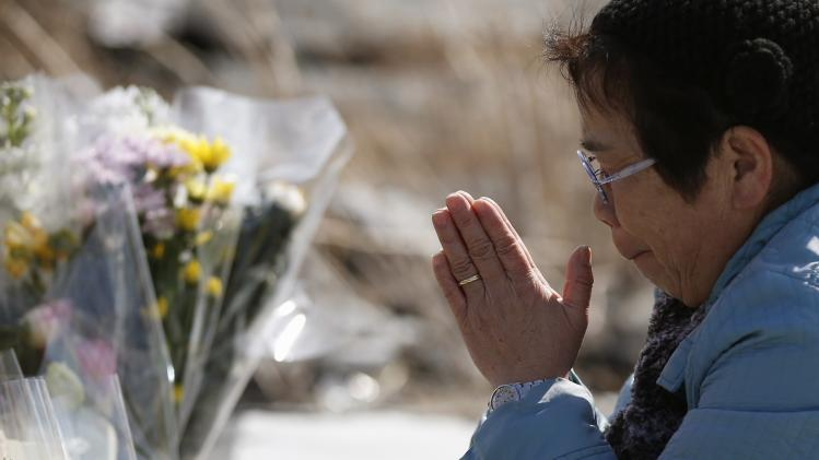A woman offers prayers for victims of the March 11, 2011 earthquake and tsunami in Namie town