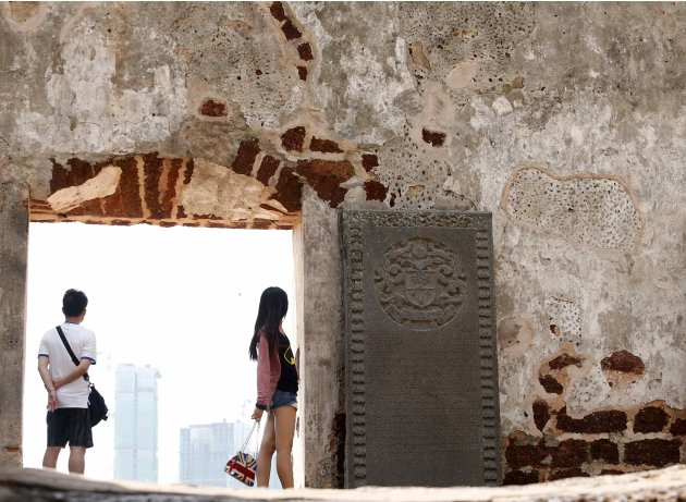 Tourists look at buildings under construction that are shrouded with light haze as they visit the Malaysia's historic St Paul Church in Malacca