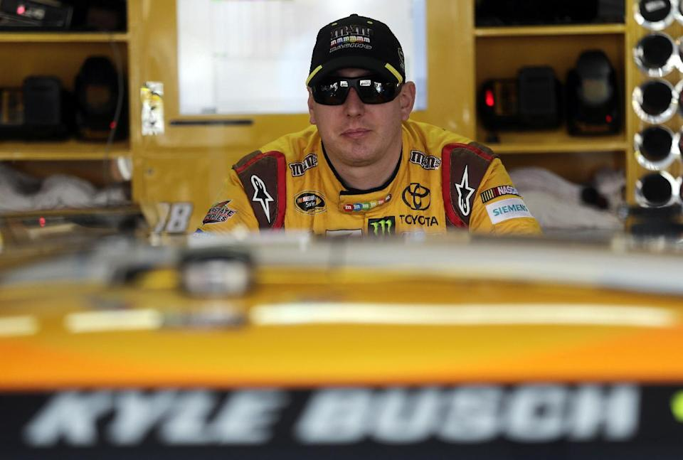 Driver Kyle Busch leans on his car as he waits during practice for Sunday's running of the NASCAR Sprint Cup Series auto race at Talladega Superspeedway in Talladega, Ala., Friday, Oct. 18, 2013.