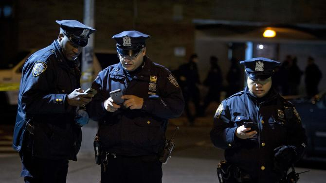 Police look at social media apps on their smart phones at the scene of a shooting where two New York Police officers were shot dead in Brooklyn, New York